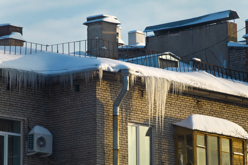 Huge icicles hang down from roof, presenting danger for the persons down.