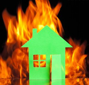 Paper house in fire on a black background concept
